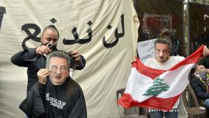 Arga demonstranter har tagit på sig masker med den korruptionsmisstänkta centralbankschefen Riad Salamehs ansikte under en protest i Beirut.