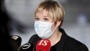 Kulturminister Annika Saarikko (C) talar i mikrofon med munskydd på.