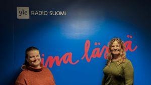 Kaksi naista seisoo Radio Suomen logon edessä ja katsoo kameraan.