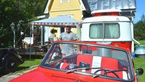 Sami Tikkanen vid en av sina gamla bilar och en husvagn framför Café Classic Garage i Snappertuna.