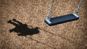 På bilden synns asfalt och på asfalten skuggan av ett gungande barn. Själva gungan synns också, men den är tom.