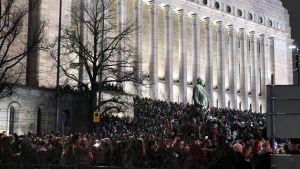 Folk följer med nyårsfirandet från Riksdagshusets trappa.