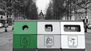 Insamlingslådor för glas, metall och brännbart på rad.