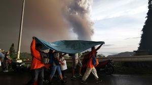 Människor i staden Tagaytay skyddar sig för askan från närliggande Taal.