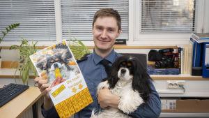 Palomestari esittelee oikeassa kädessään Asunnossa lemmikkieläimiä tarroja. Vasemmalla kädellään hän pitelee sylissään koiraa.