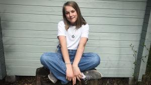 Nadya sitter på en stubbe med benen i kors och ler mot kameran
