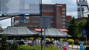 En röd flervånings tegelbyggnad med ställningar med metallvinschar på varsin sida om sig. Framför byggnaden svarta tält med polsk text och människor i vita skyddskläder samt parkerade bilar.
