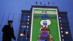 Bild på polis med munskydd utanför byggnad där en stor bild av satirtidningen Charlie Hebdos uppslag projiceras på fasaden till minne av Samuel Paty.