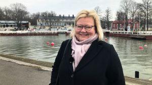 Anne Sjöström står vid gästhamnen i Nådendal med Brunnshuset i bakgrunden