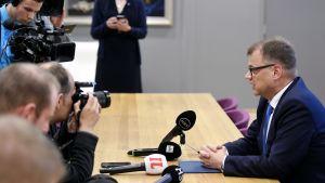 Juha Sipilä sitter vid ett bord. Fotografer på andra sidan bordet.