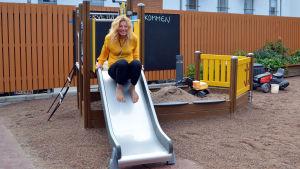 en kvinna tänker åka ner för en rutschkana i en liten lekpark