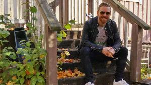 Tomi Kaukinen istuu kesällä puutalon rappusilla.