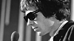 Scott Walker 1960-luvulla lähikuvassa mikrofoni kädessä. Kuva dokumenttielokuvasta.