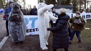 Maria Ohisalo omkramad av demonstrant i isbjörnsdräkt.