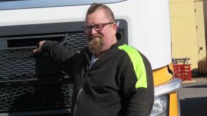 En man med kort och delvis snaggat hår, skägg och glasögon står framför en lastbilshytt. Han är klädd i arbetskläder i svart och neongult.