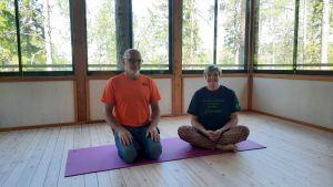 Ett par sitter i lotusställning på en yogamatta i en sal