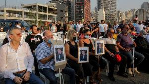 En grupp människor håller en tyst minut för offren i explosionen i Beirut.