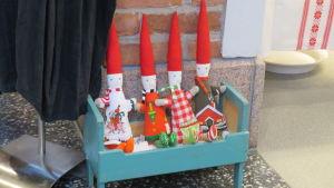 Fyra tygtomtar placerade i en turkosblå dockssäng  inne i en butik. Som prydnad.