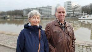 Aino och Seppo Saaro, en par med grånande hår står vid åstranden i Åbo en kall novemberdag.