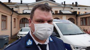 Tobias Karlsson, en man med mörkt hår munskydd och polisuniform står framför en polisbil.