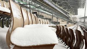 Snö på en sittplats på Tölö fotbollsstadion.