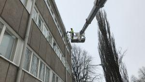 Jarmo Rantala på Länsirannikon kiinteistöpalvelu röjer snö från ett tak på Malmögatan i Vasa.