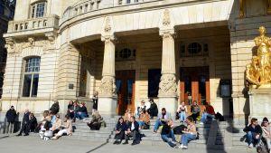 Människor sitter på trapporna till Dramaten och njuter av vårsolen.