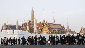Omkring 200 000 sörjande, svartklädda thailändare tog farväl av sin kung i Bangkok