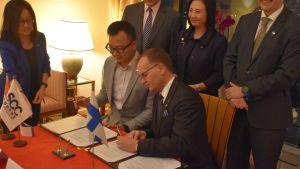 Tekes generaldirektör Pekka Soini skriver under ett avtal med Hongkongkonsortiet Smart City.
