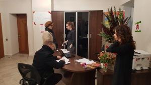 Personer står och diskuterar i Ksenia Sobtjacks valbyrå.