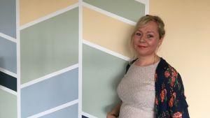 Kvinna står vid vägg  med grafiskt mönster.
