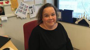 hanna karlsson ler för kameran iklädd svart klädsel på sitt kontor i åbo
