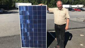 Solpanelsförsäljare Ari-Jussi Uunila förevisar solpanel.