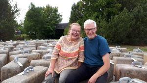Tiina ja Kimmo Linkama istuvat matkalaukkuilta näyttävien betoteosten päällä