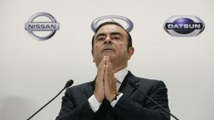 Carlos Ghosn står med knäppta händer framför en Nissan-skylt.