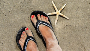 kvinnliga fötter nergrävda i sanden, brevid fötterna finns en stjärnformad snäcka.