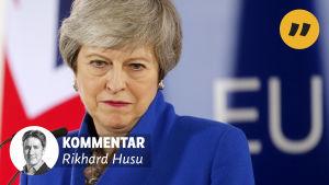 Theresa May ser besviken ut med en vägg med texten EU på bakom sig.