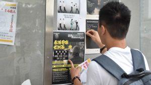 En Honkongbo sätter upp planscher.