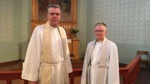 Prästerna Mikael Forslund och Rose-Maj Friman iklädda albor i Brändö kyrka i Vasa