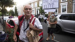 Dominic Cummings utanför sitt hem i London i bakgrunden står en demonstrant