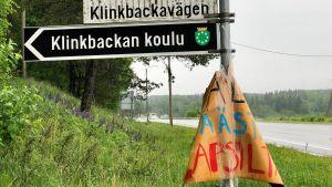 En vägskylt med finsk och svensk text. Nedanför vägnamnen står det på en svartvit skylt Klinkbackan koulu. Till höger löper en asfaltväg. Regnig väder. Grön försommarmiljö.