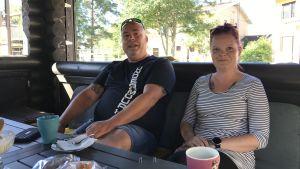 En kvinna och en man sitter i en grillstuga.