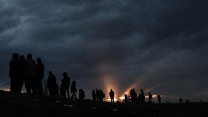 Tummia pilviä vasten näkyy pakolaisten silhuetteja