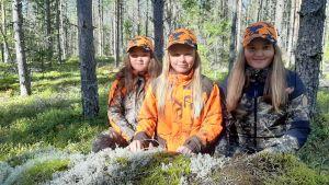 Tre flickor i jaktkläder i skogen.