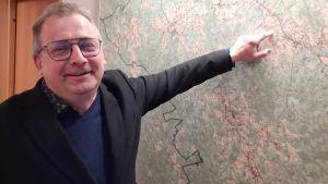 En man med glasögon pekar på en väggkarta över Pedersöre