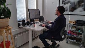 En man som sitter vid en dator i ett öppet kontorslandskap. Han har mössa på huvudet, ryggen vänd mot kameran.