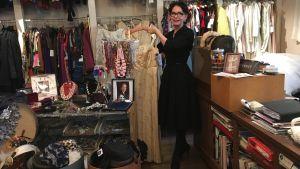 Arja Könönen visar en klänning i sin vintageaffär.