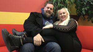 Stan Saanila och Satu Söderström i röd soffa. Satu har benen i Stans knä. I bakgrunden ful randig röd-orange-gul vägg på Yle och en krukväxt.
