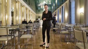 Sanna Marin, en ung kvinna i svart kavaj, svarta byxor och svarta högklackade skor står i en stor sal med många bord och stolar. Salen är kantad av pelare på ena sidan.
