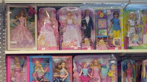 En hylla fylld med olika sorters lådor med Barbie dockor i.
